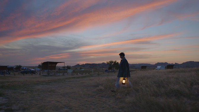 """A woman walks through a field with a lantern in the movie """"Nomadland"""""""