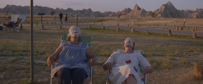 """A still from """"Nomadland"""" of two women sitting in lawn chairs in field wearing face masks and with cucumbers on their eyes."""