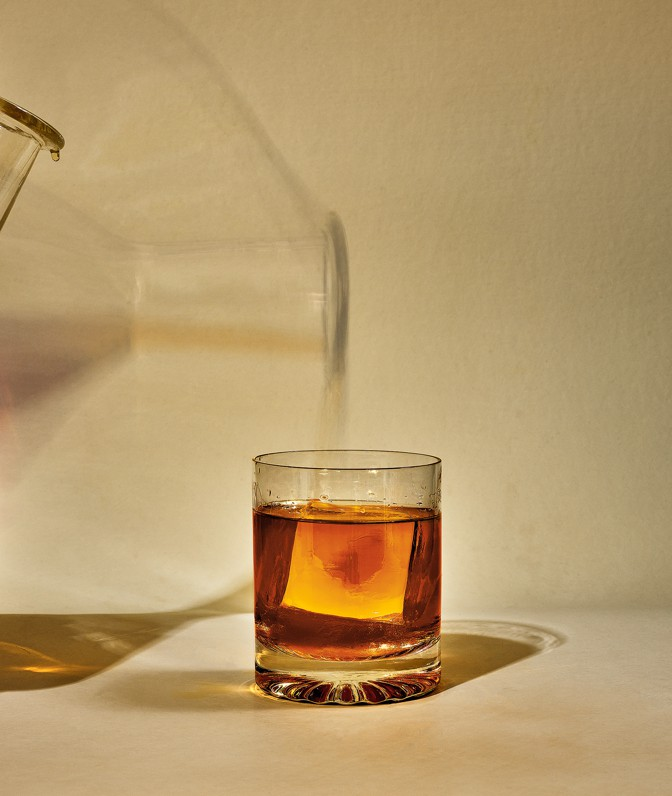 photo of brown liquor poured from beaker into highball glass with large square ice cube