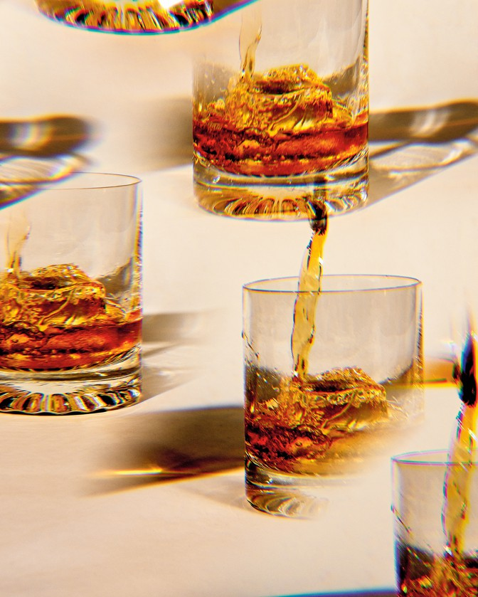 photo of brown liquor being poured over ice