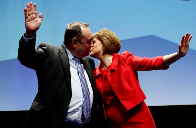 Man and woman greet on stage with hands up