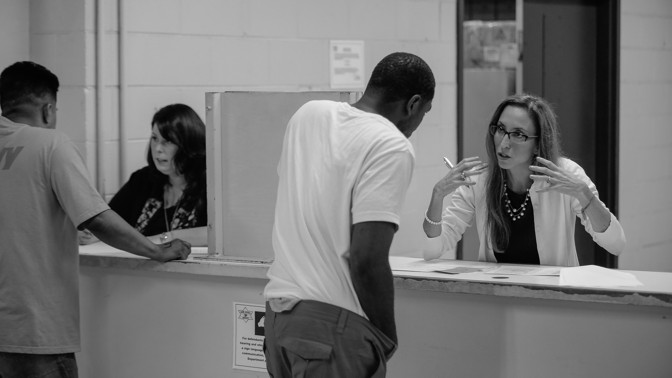 An employee of the the Sheriff's Office of Mental Health Policy and Advocacy, right, speaks with a detainee at the Cook County Jail. The black and white photo shows the employee motioning and the man leaning in to hear her.