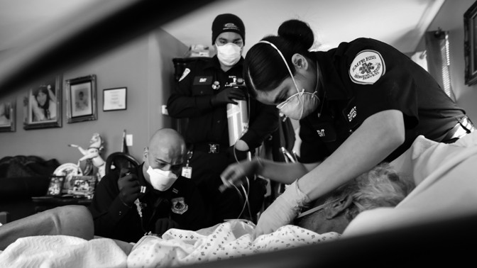 Three paramedics intubate a gravely ill COVID-19 patient.