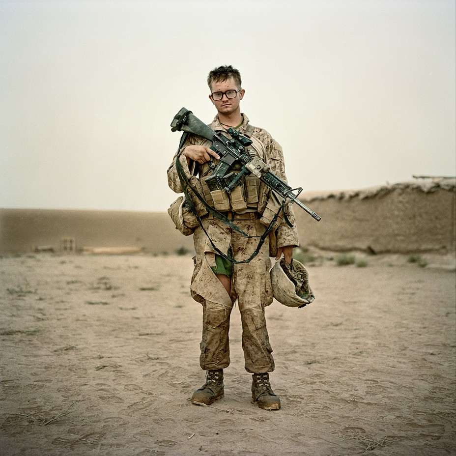 Marine wearing glasses geared up and holding rifle and helmet, pants torn