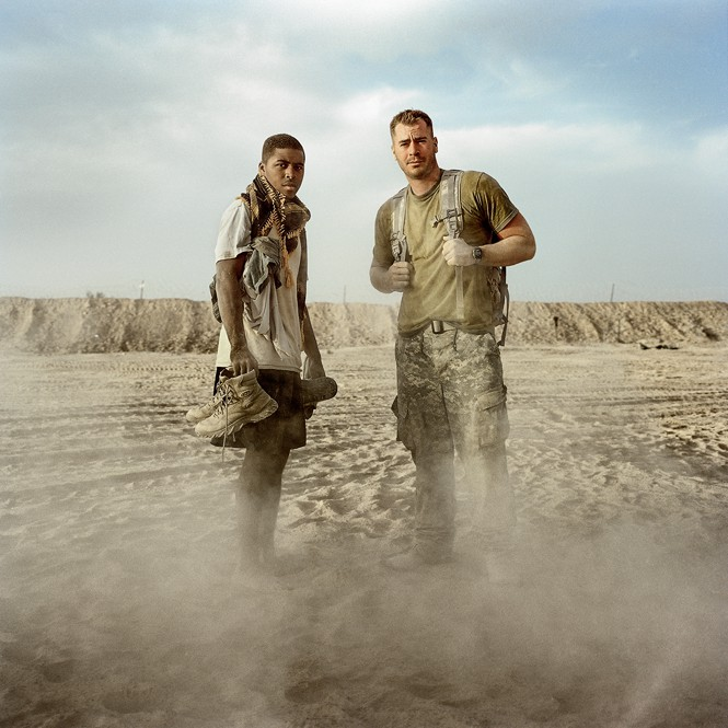 Two soldiers standing together, one holding boots in hands and one wearing backpack, with dust rising from ground