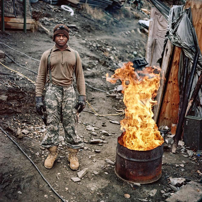 Soldier wearing hat, gloves, boots stands near half an oil drum with high flames burning