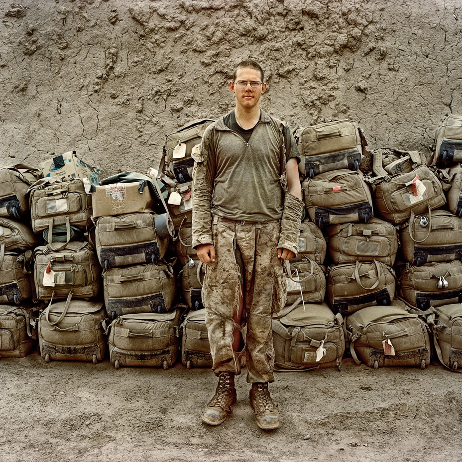 Soldier with torn shirt and pants standing in front of a pile of khaki-colored wheeled duffel bags