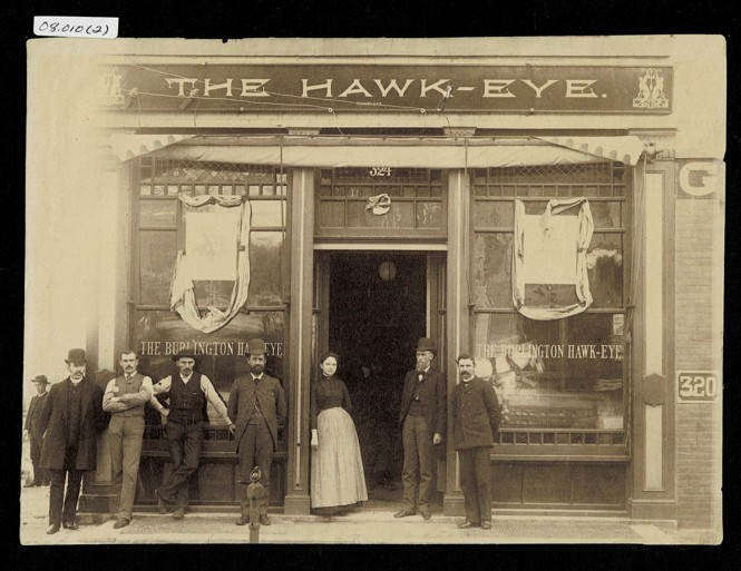 Old photograph of people standing in front of the former Hawk Eye building.