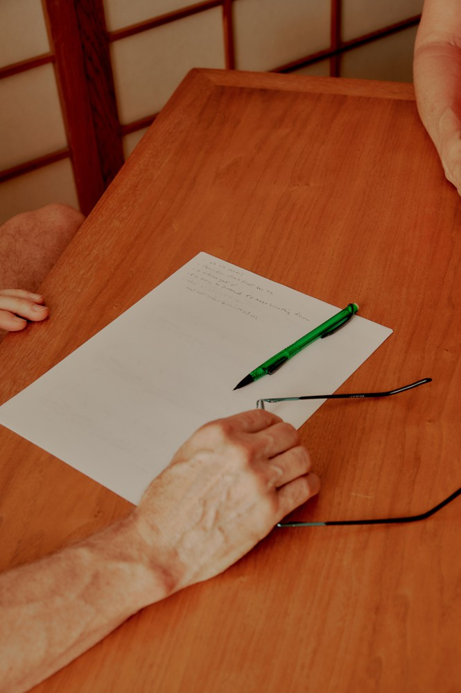 A hand holds glasses on a table next to a piece of paper