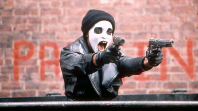 """A man in a face mask holds two guns, from the movie """"Dead Presidents."""""""