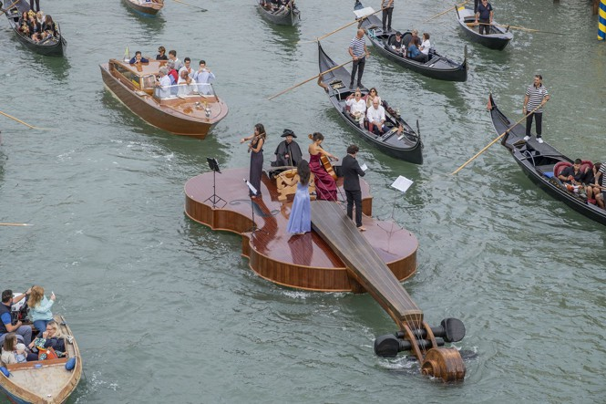 A violin-shaped boat parades near the Accademia Bridge in Venice, Italy.