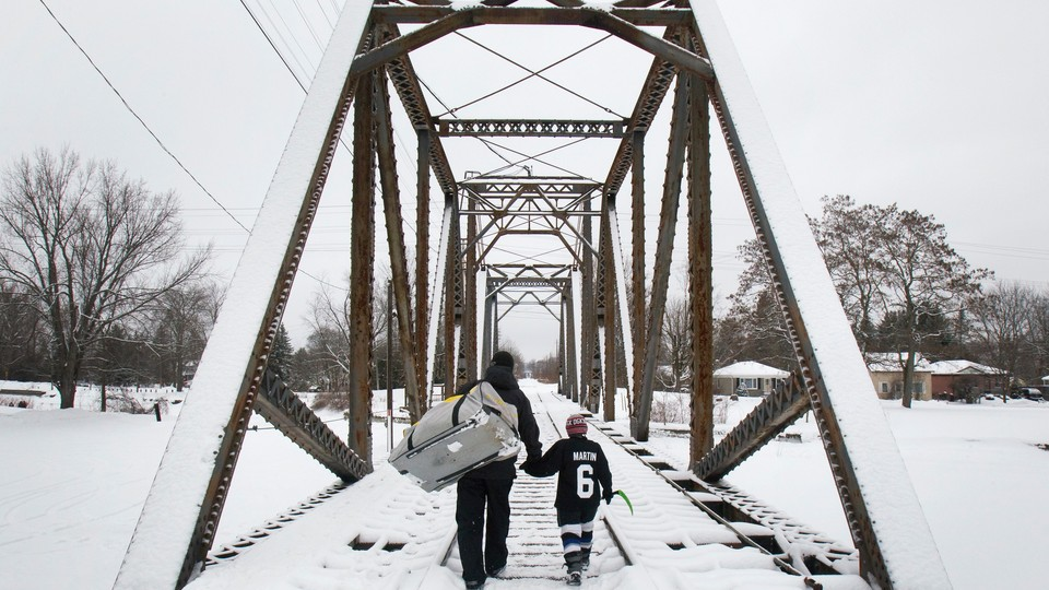 A man and a little boy hold hands while crossing a snowy bridge.