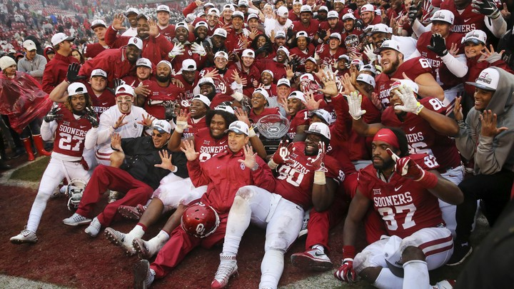 The Oklahoma Sooners pose for a photo with the Big 12 Championship trophy.