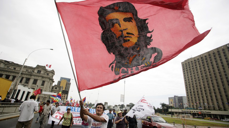 A man carries a flag with the image of Che Guevara during a march against Peruvian President Alan Garcia in downtown Lima April 13, 2010.