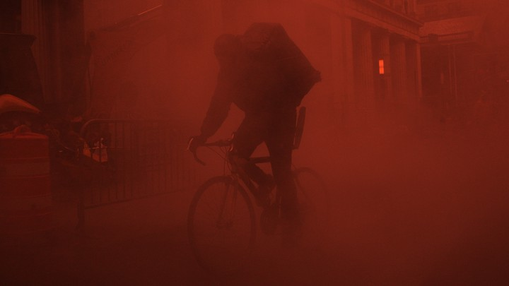A person riding a bicycle in a red fog