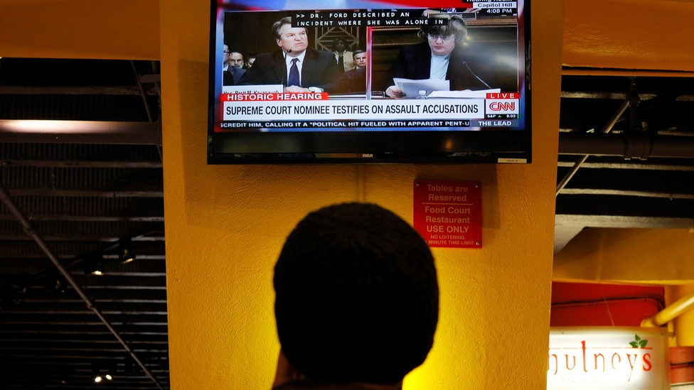 A person watches a television broadcast of the Kavanaugh hearing.