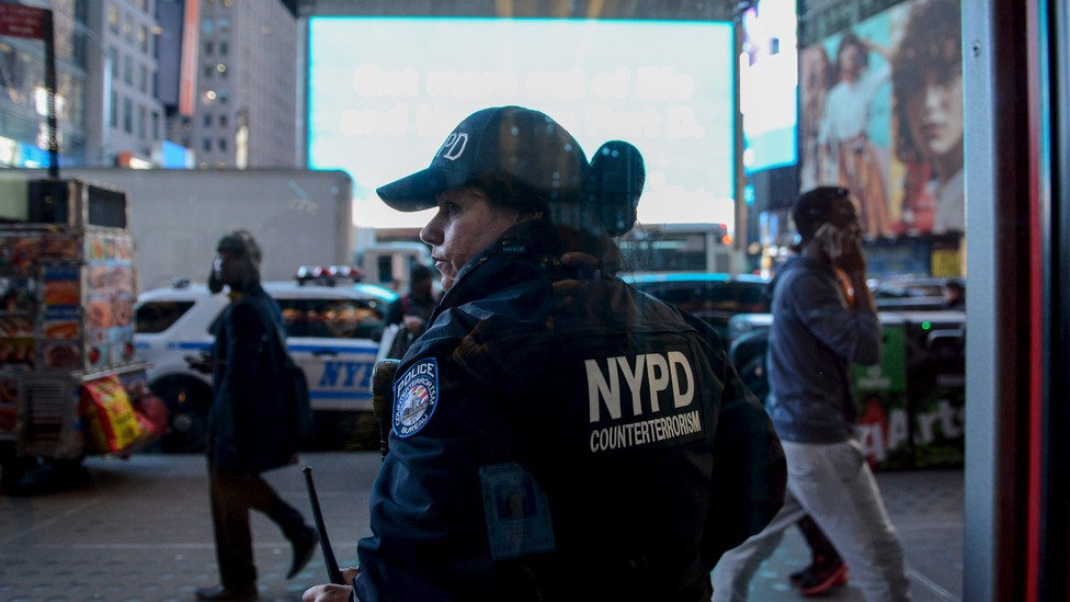 A NYPD counter-terrorism officer is seen through a window in New York City.