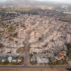 An aerial view of a neighborhood with many blocks of houses burned to the ground.