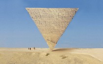 A pyramid balances on its point, upside down, in the desert with blue sky and 3 small figures