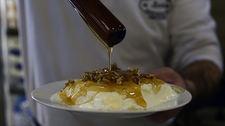 A person drizzling honey on a bowl of yogurt