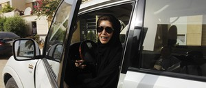 A Saudi woman gets out of her car after driving.