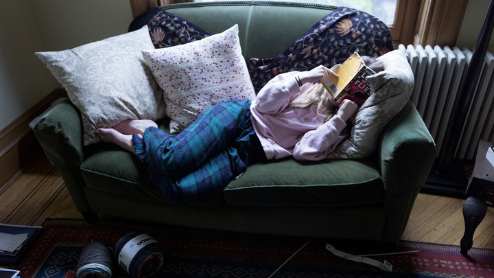 A teenager reading at home.