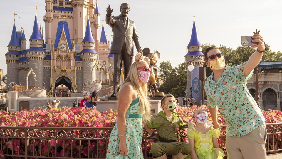 A family wearing masks takes a selfie in front of the statue of Walt Disney and Mickey Mouse at Disney World.