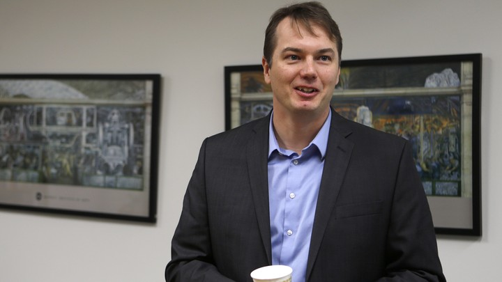 Chris Urmson standing in front of two framed pictures and holding a cup