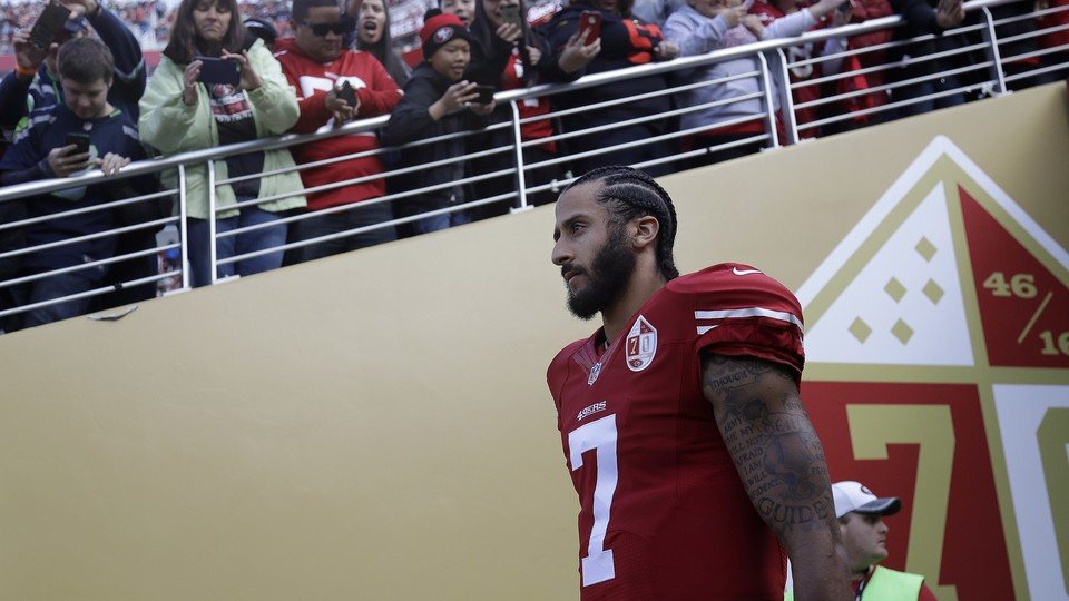 Colin Kaepernick walks out of a tunnel before an NFL football game.