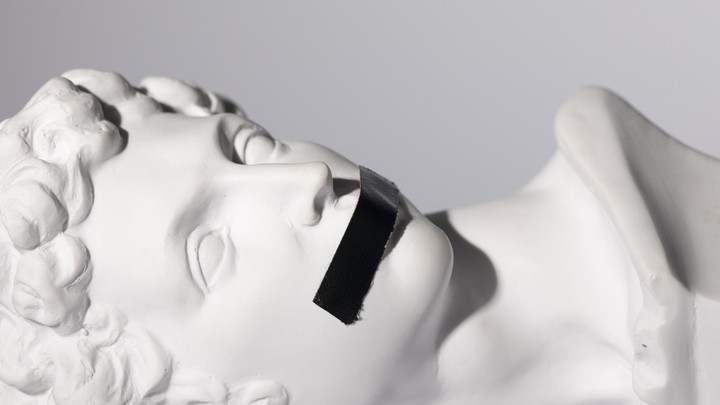 A 16th-century Michelangelo sculpture with black tape over the figure's mouth