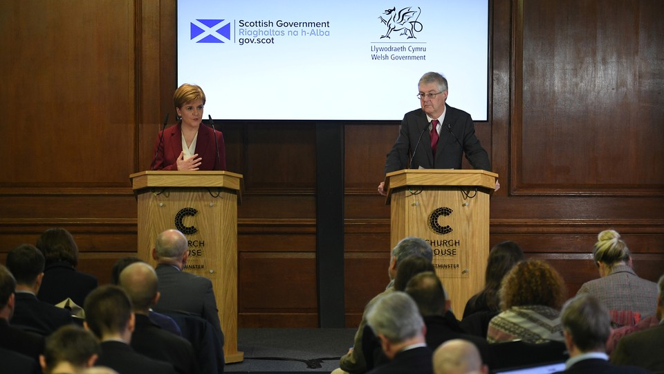 Nicola Sturgeon and Mark Drakeford stand at podiums while delivering a press conference.