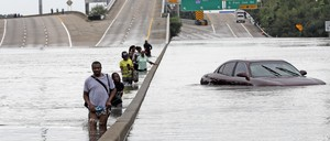 Evacuees wade down a flooded section of Interstate 610 as floodwaters from Tropical Storm Harvey rise Sunday, Aug. 27, 2017, in Houston.