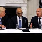 President Donald Trump, Satya Nadella of Microsoft, and Jeff Bezos of Amazon talk to each other at a table.
