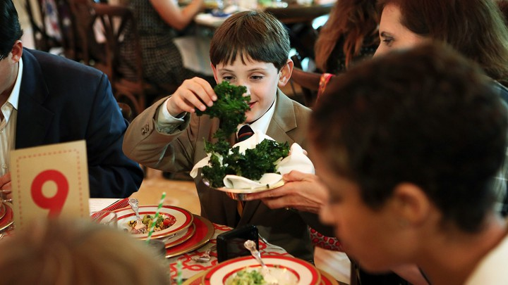 A young boy holds a leaf of kale during a meal at the White House.