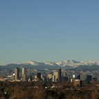 A photo of Denver's skyline with mountains in the background.