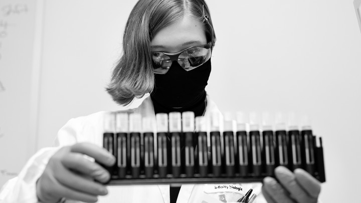 A woman in goggles with uncapped saliva samples