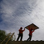 Electricians install solar panels on a roof for Arizona Public Service company in Goodyear, Arizona.