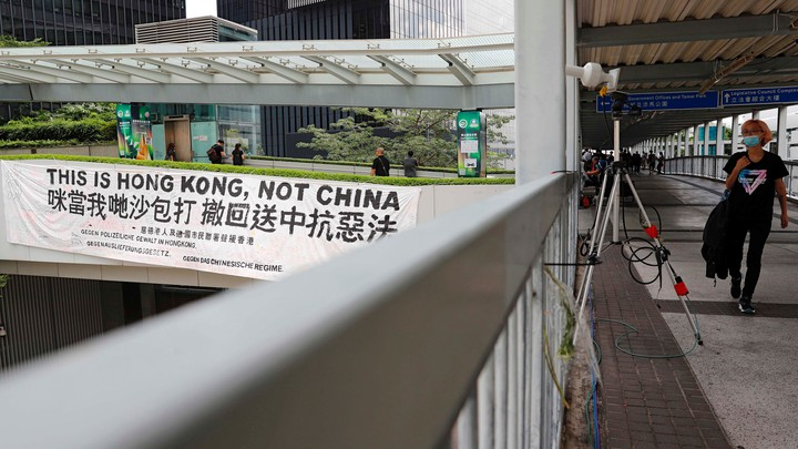 "A protester walks past a banner that reads, ""This is Hong Kong, not China."""
