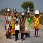 Women and girls walk down a road carrying water on the outskirts of Ahmedabad, India.
