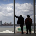 Two people in shadow look out at the river and New Jersey skyline from the Whitney Museum.