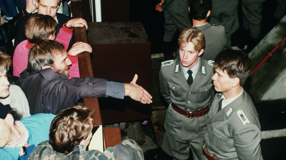 East German border policemen refusing to shake hands with a Berliner over the border fence in November, 1989