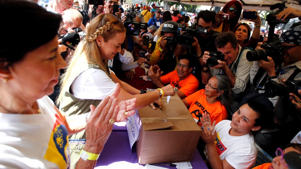 Lilian Tintori, wife of Venezuela's opposition leader Leopoldo Lopez, casts her vote during an unofficial plebiscite against President Nicolas Maduro's government and his plan to rewrite the constitution, in Caracas, Venezuela.