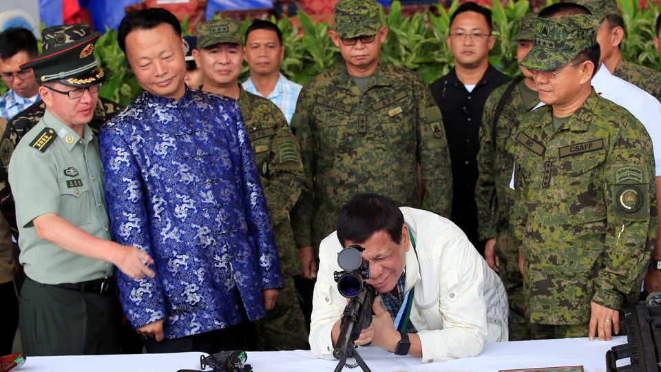 Philippine president Rodrigo Duterte checks the scope of a rifle at a ceremony marking the turnover of free Chinese military assistance to the Philippines at Clark Air Base in June 2017.