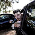 Uber drivers sit in their cars waiting for passengers.
