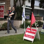 A man holding a toddler walks past open-house signs in front of condominiums for sale.