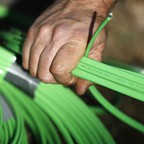 A NBN Co worker arranges fibre-optic cables used in the National Broadband Network in west Sydney.