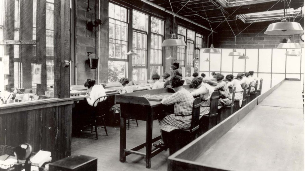 Women sitting at desks with trays