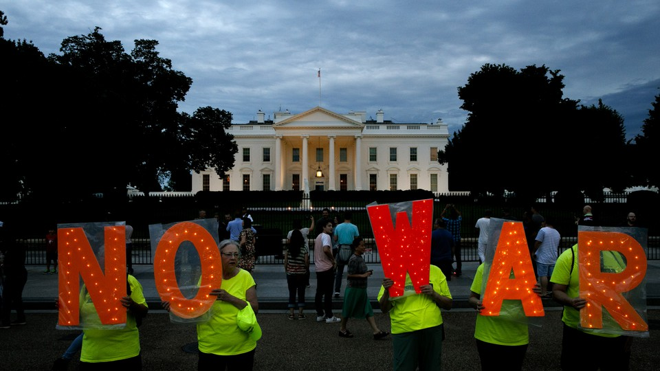 """Protesters hold signs that say """"No War"""" outside the White House on June 20."""