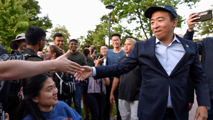 Andrew Yang shakes hands with supporters at a campaign rally.