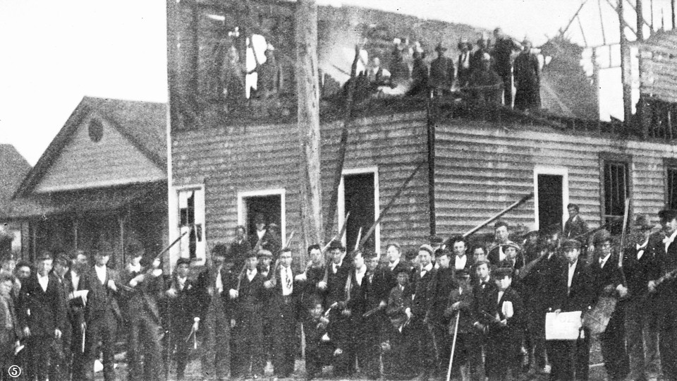Men gather outside the charred remains of The Daily Record after the 1898 massacre.